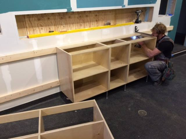 Completed sheet flooring, and Levi installing the back bar base cabinetry.